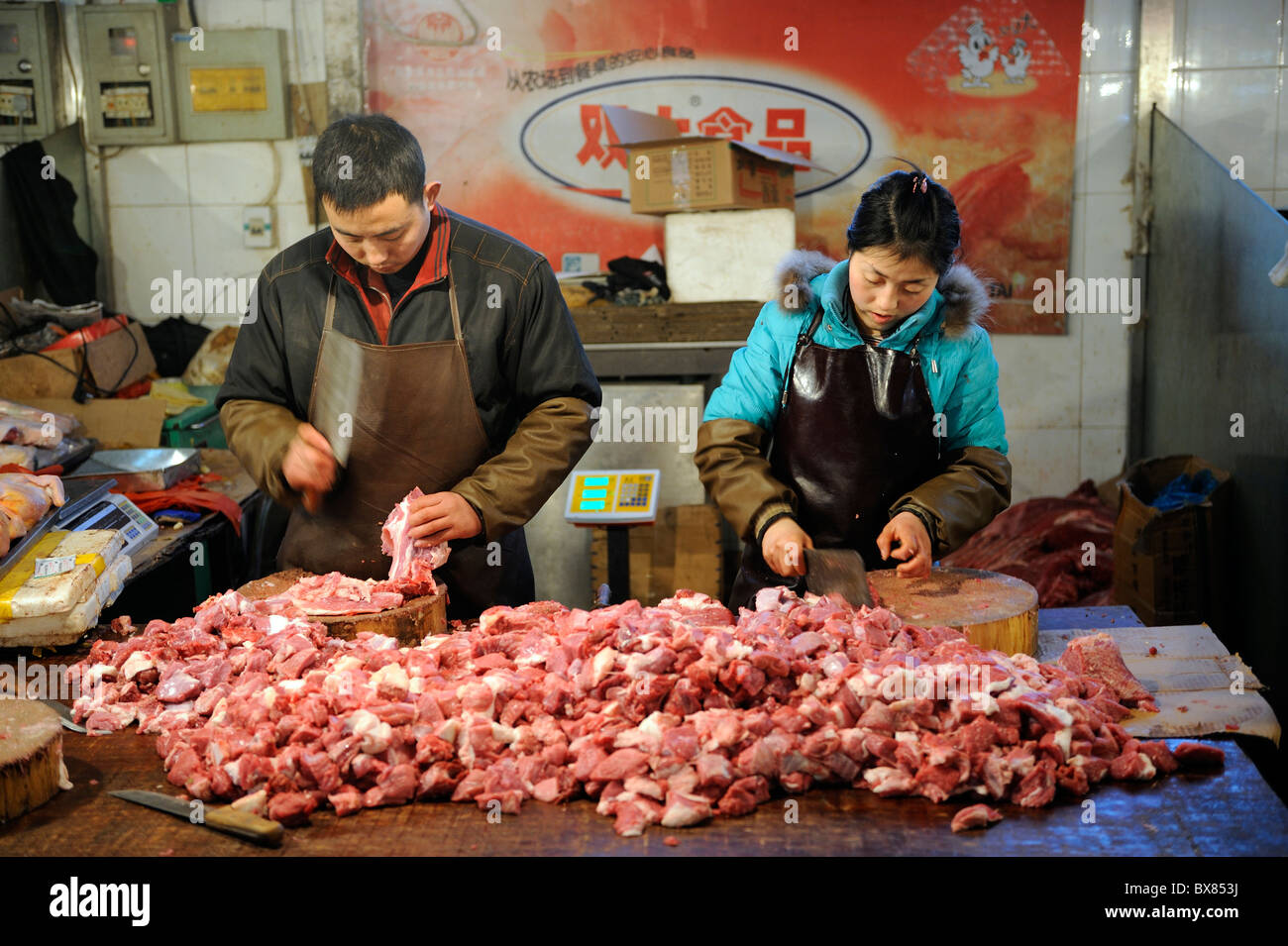Chinese vendors chop pork at a market in Beijing, China. 10-Dec-2010 - Stock Image