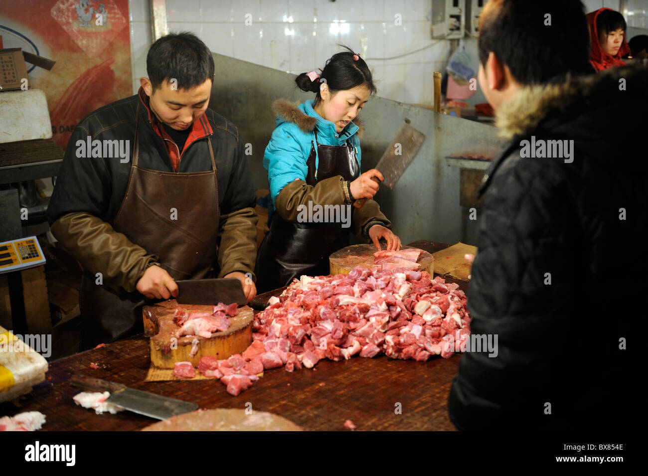 Chinese vendors sell pork at a market in Beijing, China. 10-Dec-2010 - Stock Image
