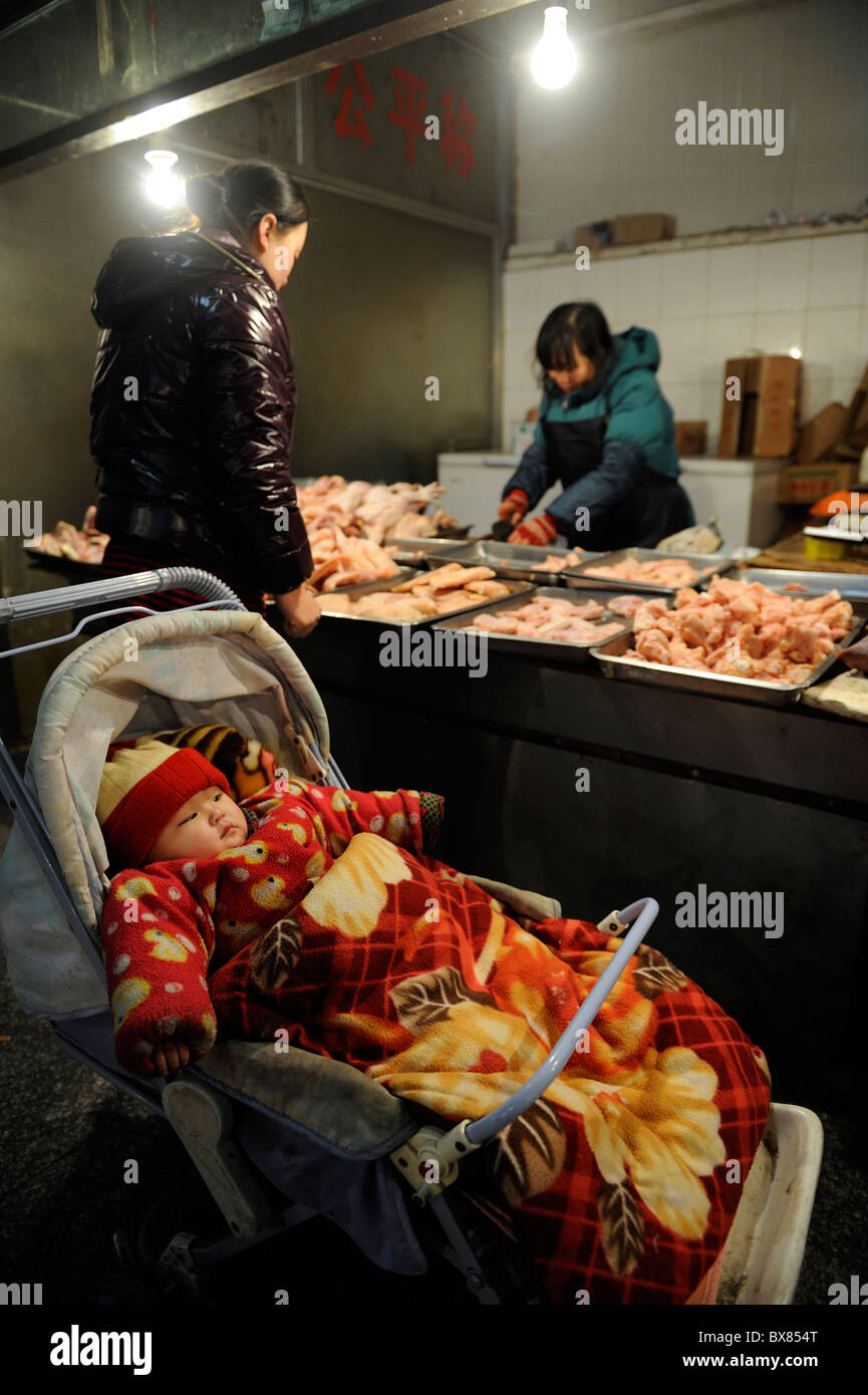 A lady buys chicken and leaving her baby in a pram nearby at a market in Beijing, China. 10-Dec-2010 - Stock Image