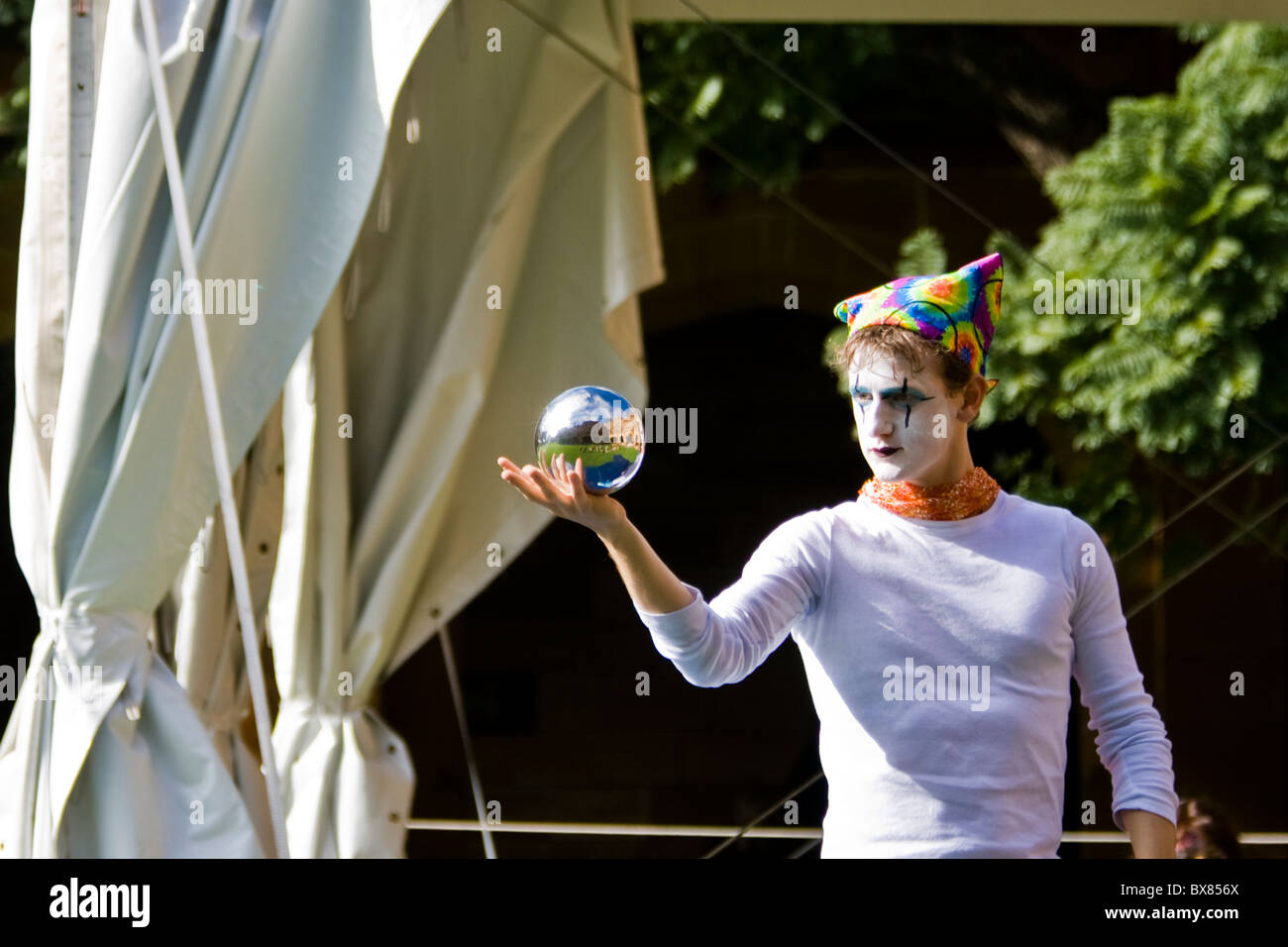 Perfomer spins a reflective ball in Sydney University open day - Stock Image