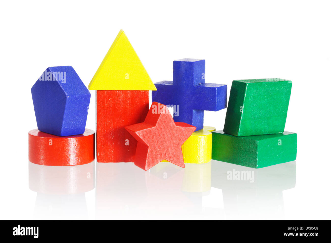Colorful geometrical blocks arranged on white background with reflection - Stock Image