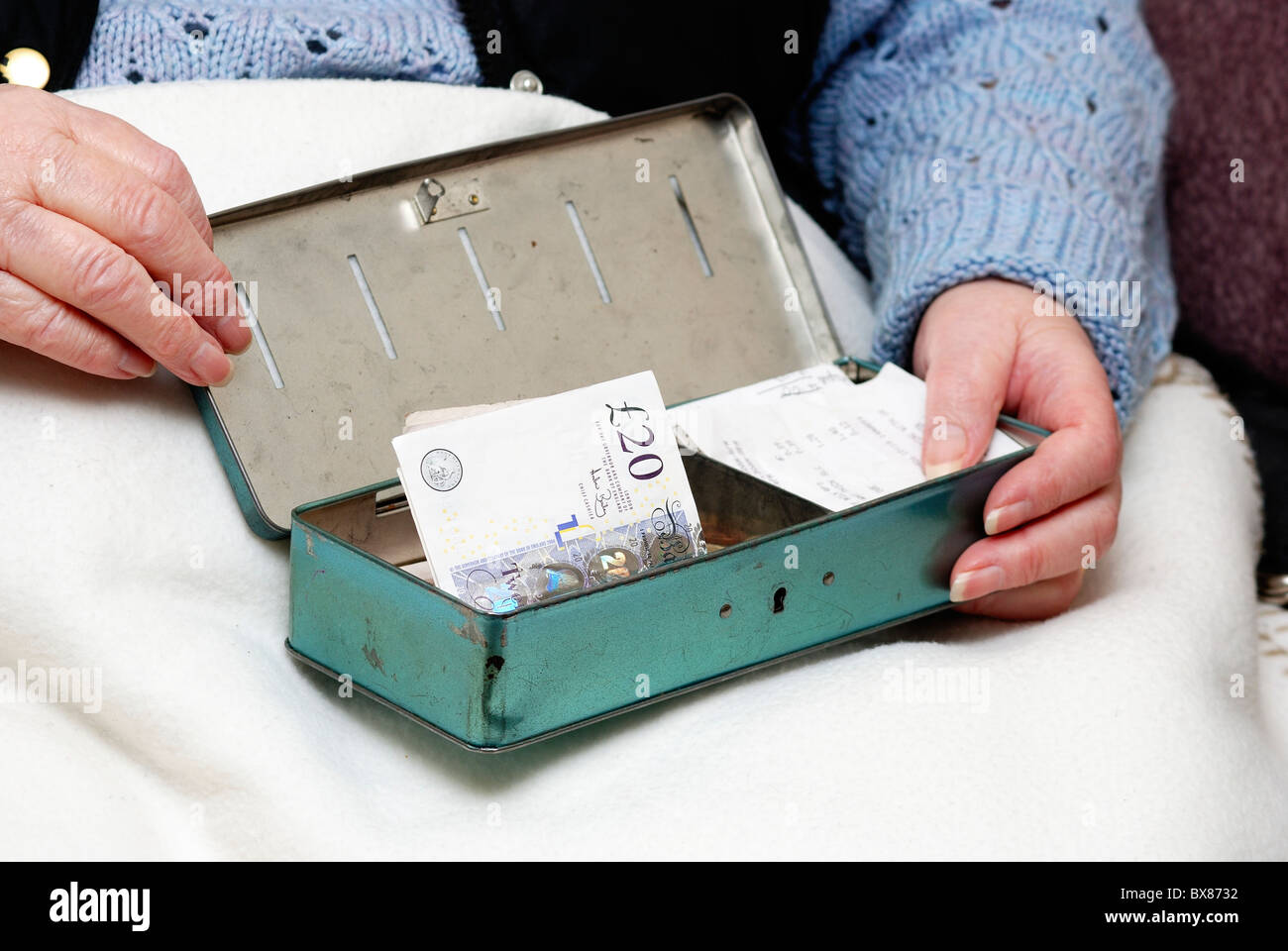 pensioner with cash tin and English currency - Stock Image