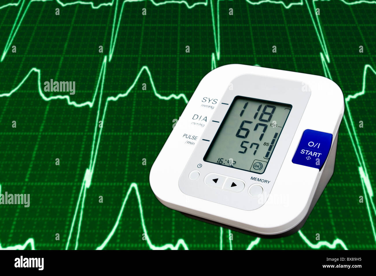 Digital blood pressure monitor with cardiogram in the background - Stock Image