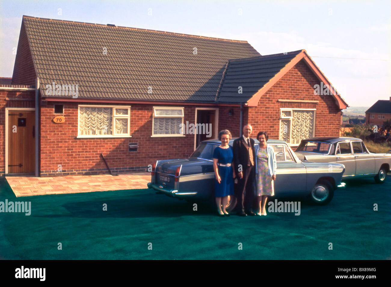 A middle class elderly couple and friend stand outside their newly built bungalow and new cars for a family portrait. - Stock Image
