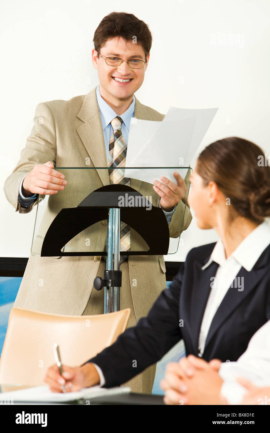 Portrait of smiling businessman holding documents and touching rostrum looking at student writing lecture - Stock Image