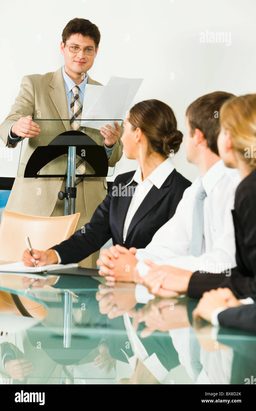 Portrait of smiling businessman holding documents and touching rostrum and students sitting at the glassy table - Stock Image