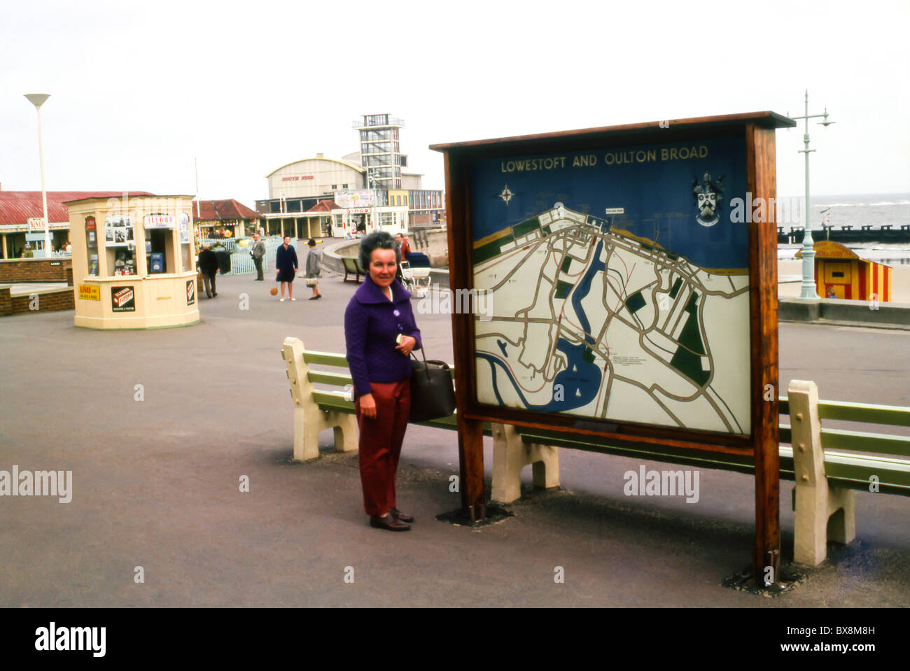 A original 1963 image of woman standing in front of the Lowestoft and Oulton tourist map board on the sea front - Stock Image