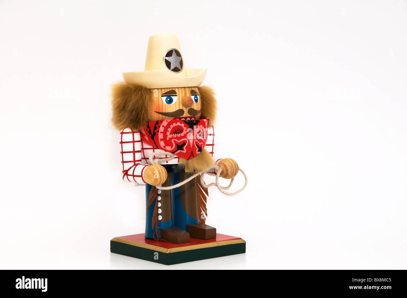 A charming holiday nutcracker dressed in western clothing and wearing a sheriff hat and red bandanna scarf holds - Stock Image