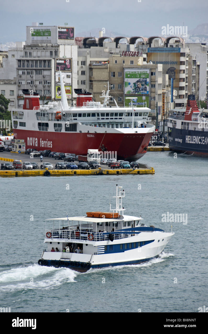Nova Ferries car and passenger ferry Phedra berthed in Piraeus harbour with harbour tour vessel cruising by Stock Photo