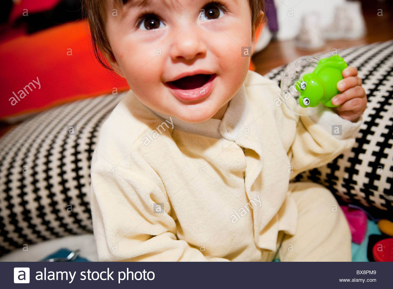 Baby girl holding a frog toy - Stock Image