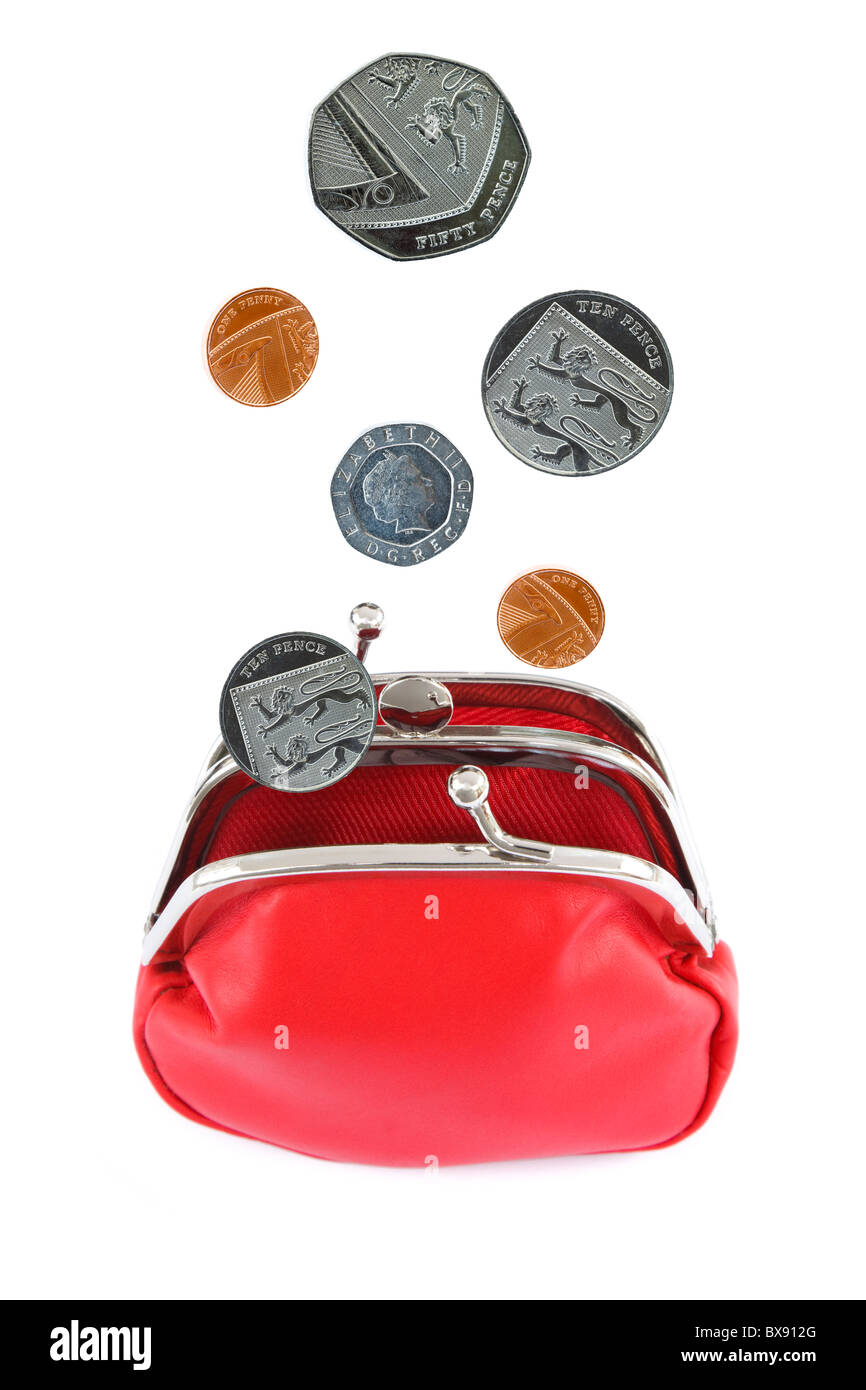 Sterling coins falling in to an open red coin money purse cut out isolated on a white background. England, UK, Britain - Stock Image