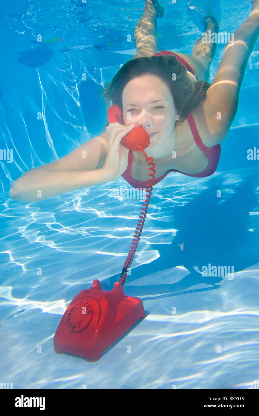 Woman answering a red telephone underwater - Stock Image