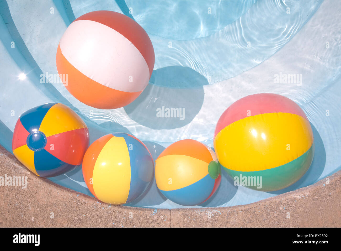 Beach balls in a blue swimming pool - Stock Image
