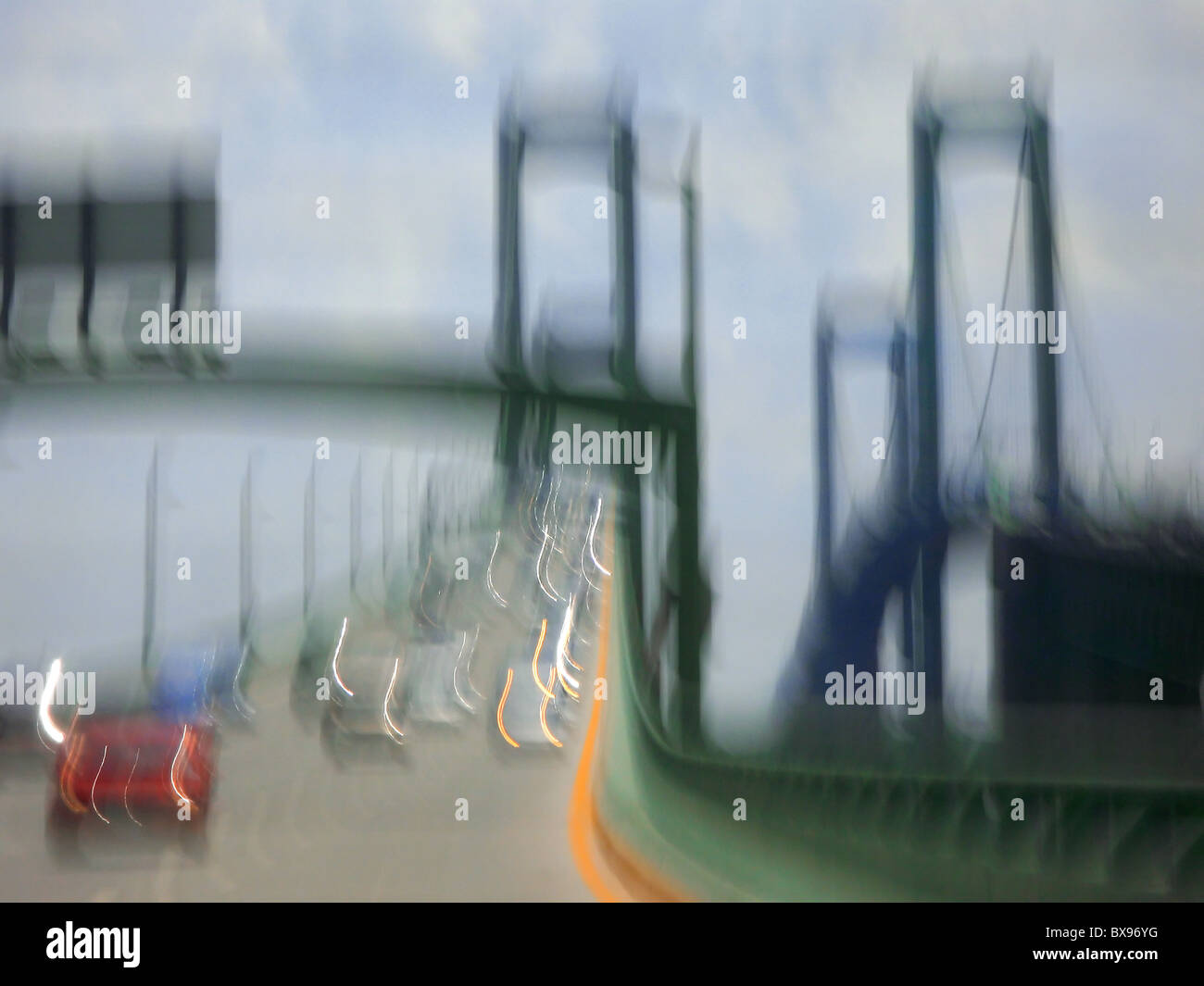 View of a bridge in New York City against a blue with Motion blur and three towers and communting cars near with - Stock Image