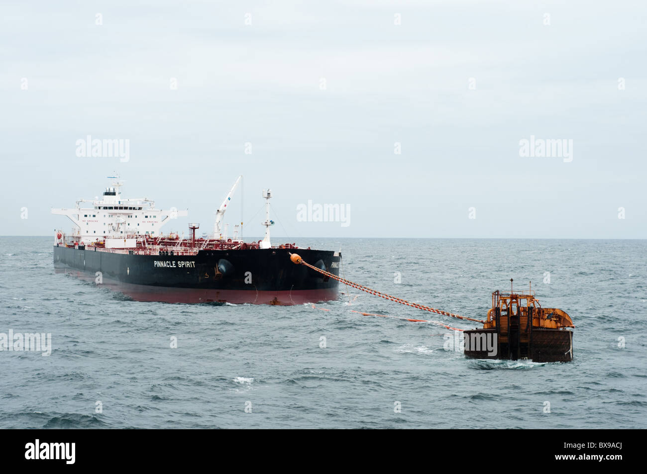 Oil tanker ship anchored in offshore area waiting to be loaded by a production oil rig from petrobras, brazilian - Stock Image