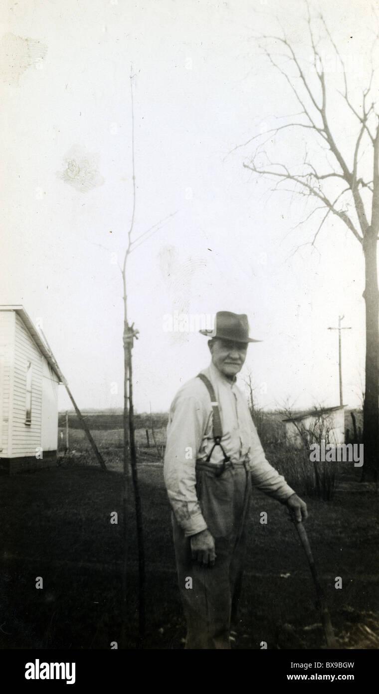 Old man with cane on farmstead farmer eldery male fashion suspenders Stock Photo