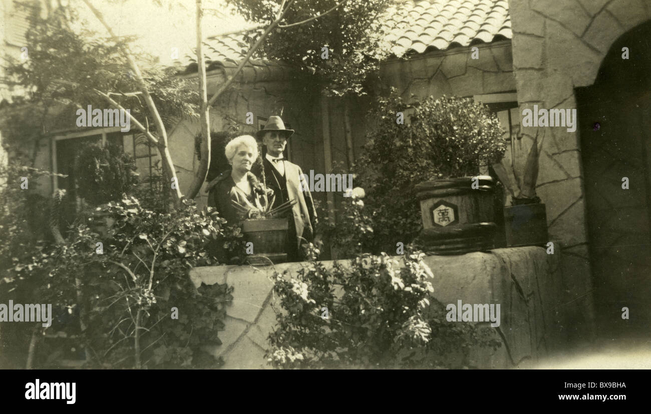 older couple 1920s 1930s exotic plants asian garden house stone Americana black and white - Stock Image