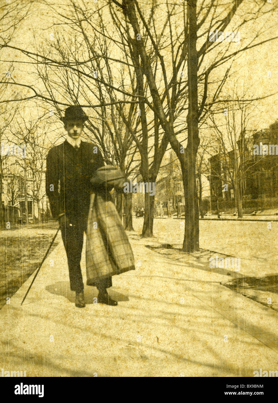 man dressed in black hat fashion walking on sidewalk during 1890s Americana black and white - Stock Image