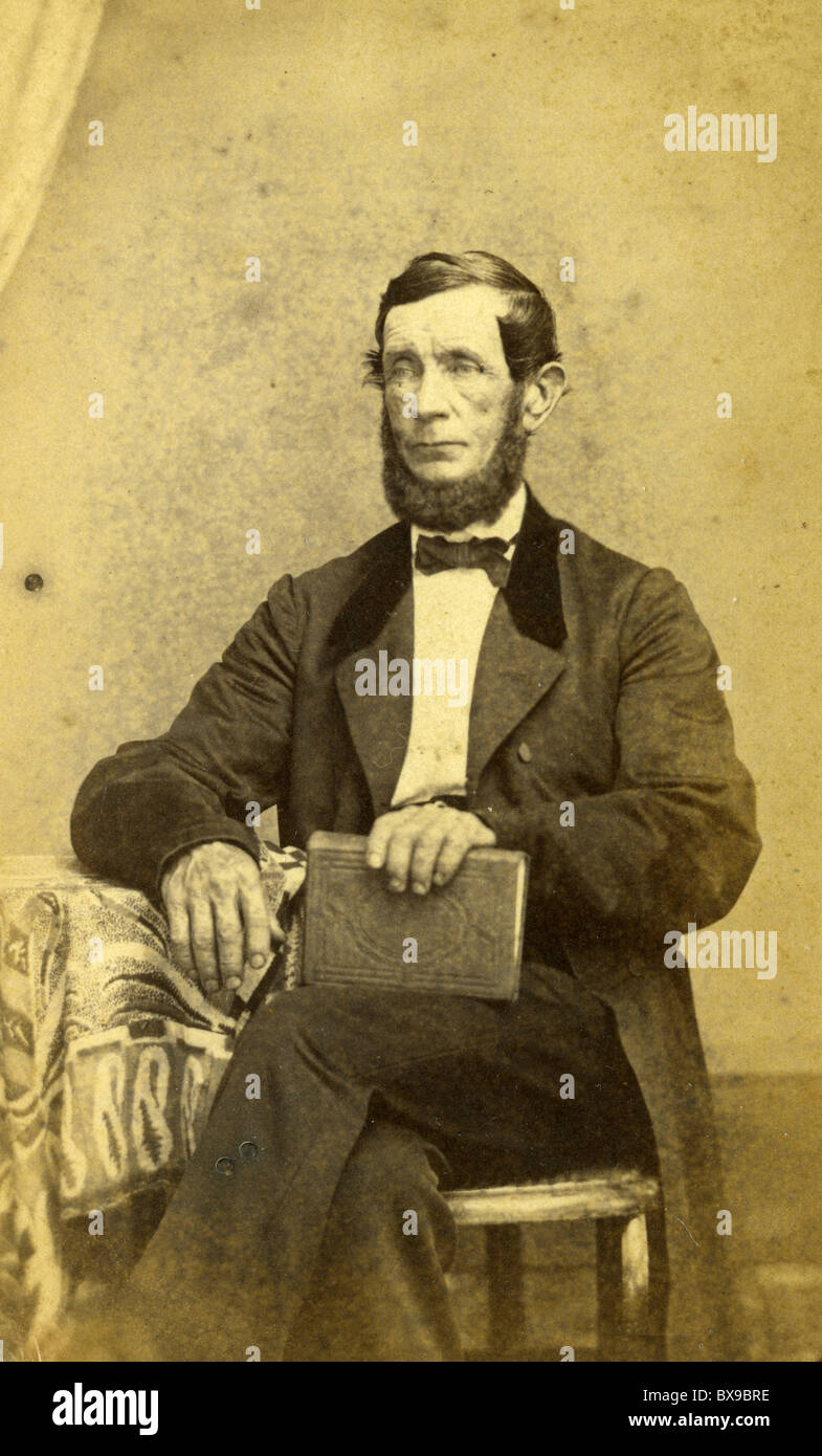 Man wearing black coat photograph 1860s fashion bow tie male seated portrait Americana black and white - Stock Image