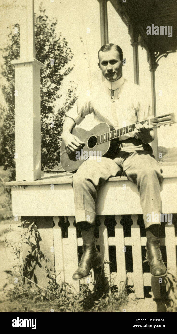 Man sitting on wood porch playing guitar during the 1920s 1930s folk musician music Americana black and white - Stock Image