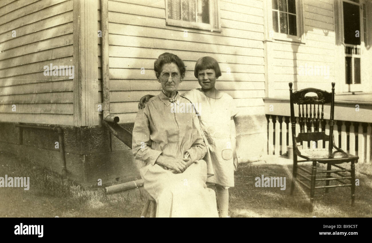 grandmother and granddaughter 1920s 1930s rural America wood chair house architecture generations Americana black - Stock Image
