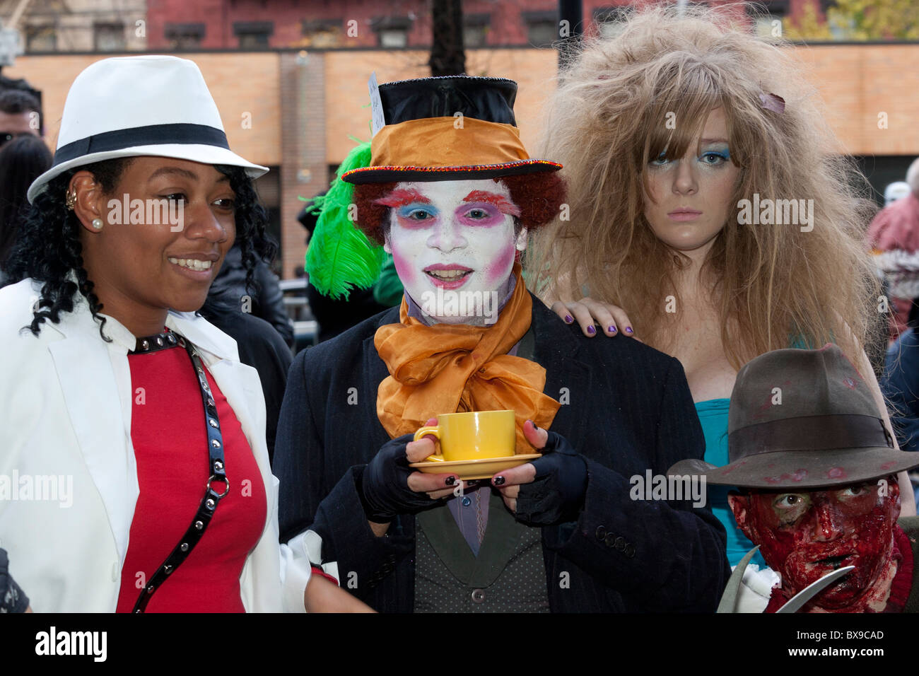 Alice, the Mad Hatter, and Freddy Krueger pose with a spectator at the 2010 Village Halloween parade in Greenwich - Stock Image