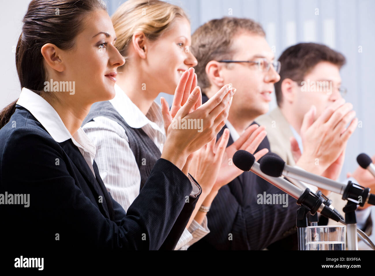 Portrait of several confident people clapping their hands - Stock Image