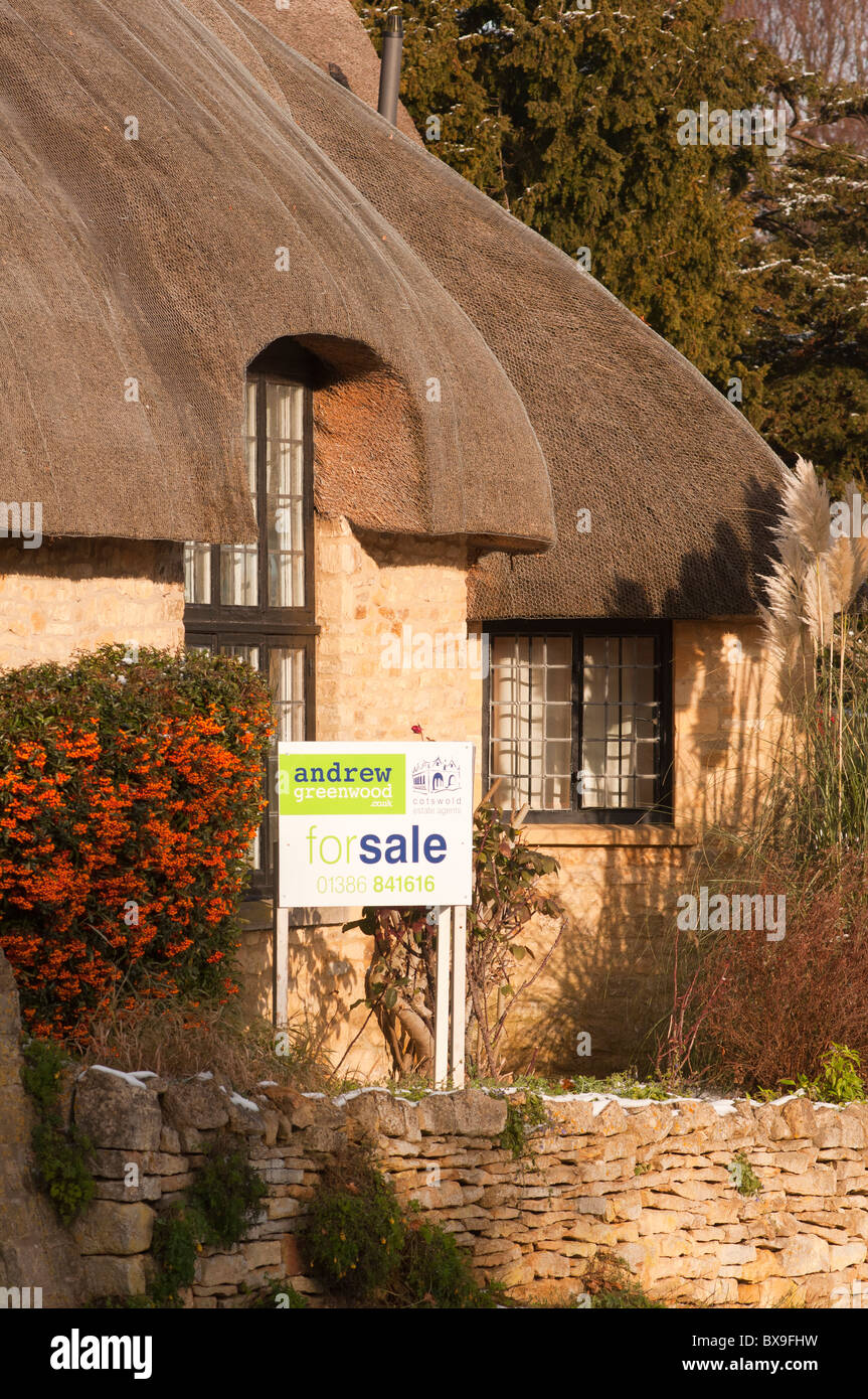 A 'For Sale' board on a thatched cottage in the Cotswold village of Broadway. England. A typical second - Stock Image