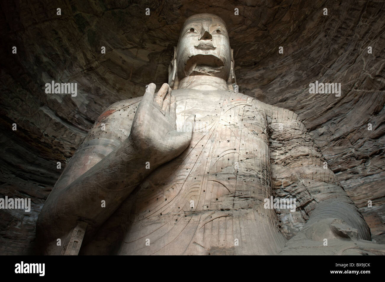 Giant Buddha statue carved inside the ancient Yungang Grottoes, Datong, Shanxi, China. - Stock Image