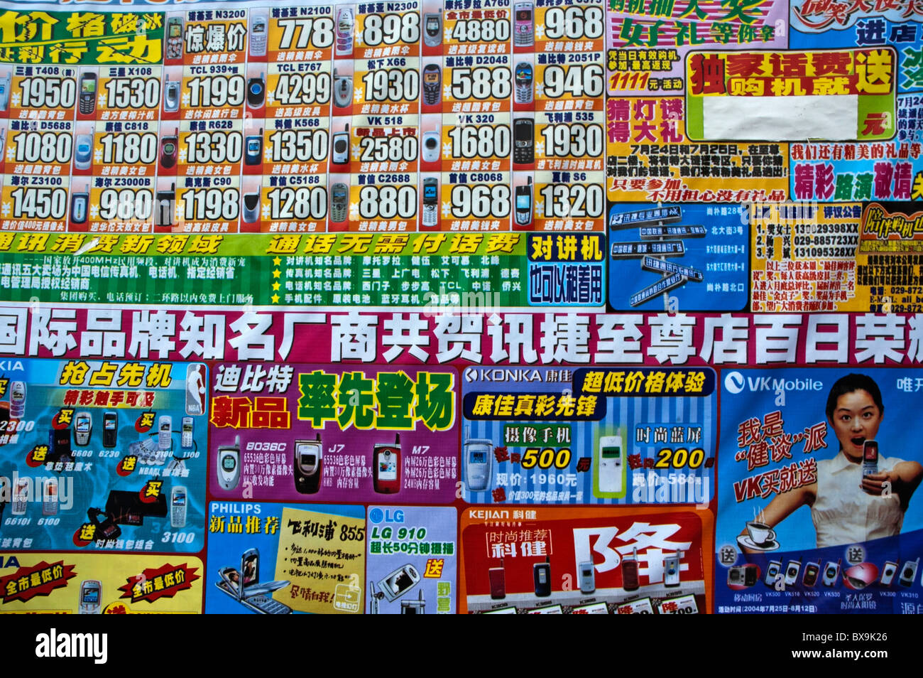Colourful posters advertising consumer electronics and mobile phones in the street, Xi'an, Shaanxi, China. - Stock Image