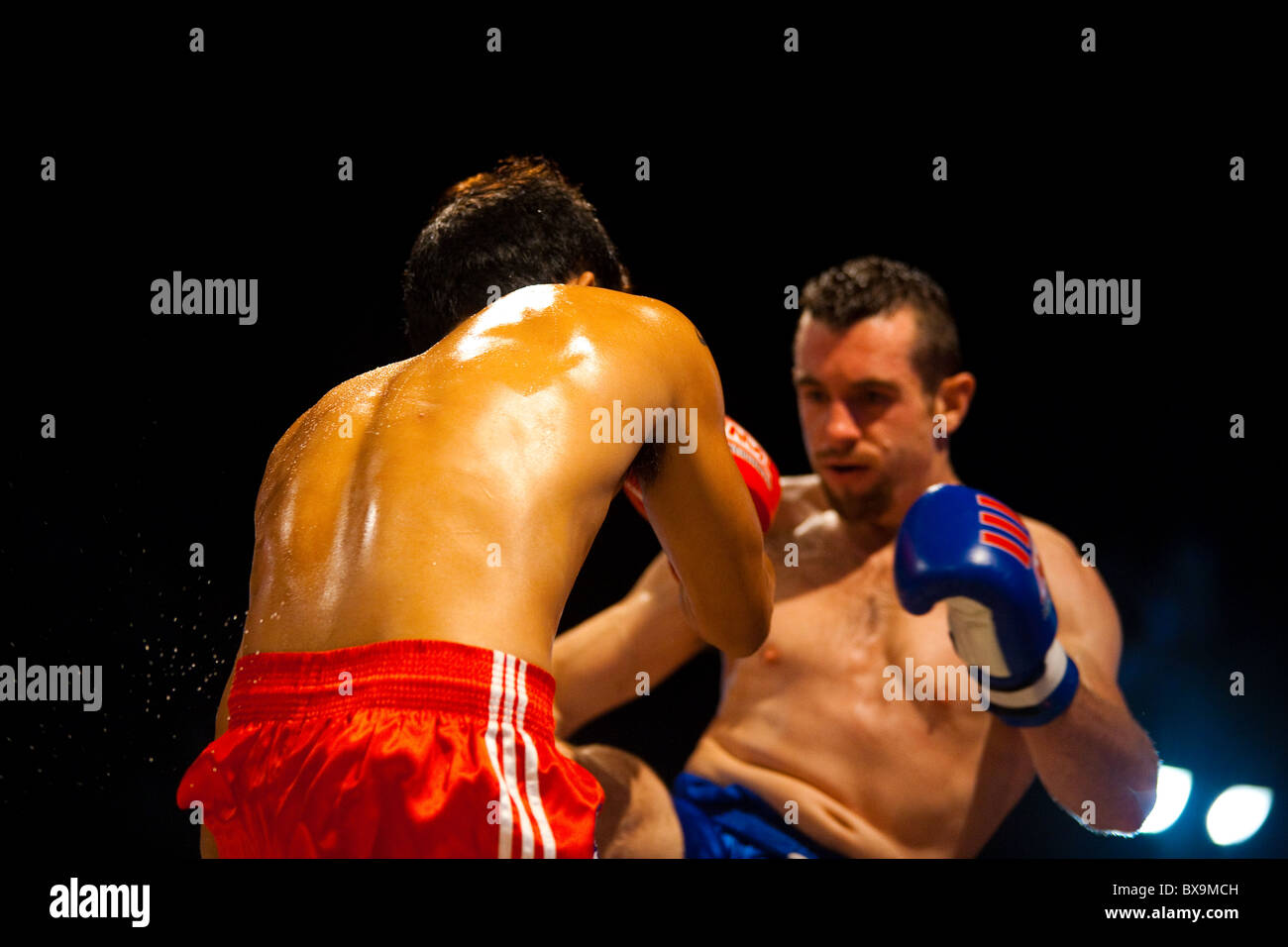 Caucasian kick to the ribs sending perspiration flying off the back of muay thai fighter - Stock Image