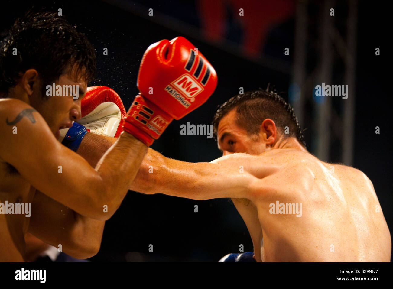 Left jab from Caucasian muay thai fighter landing on face of Asian kickboxing opponent at amateur outdoor fight - Stock Image