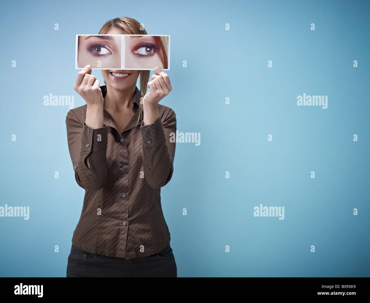 woman holding photo of cross eyes on blue background. Copy space - Stock Image