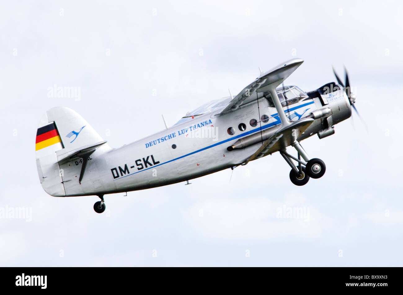 Antonov An-2T biplane in the colours of Lufthansa climbing after take off at Duxford Flying Legends Airshow - Stock Image