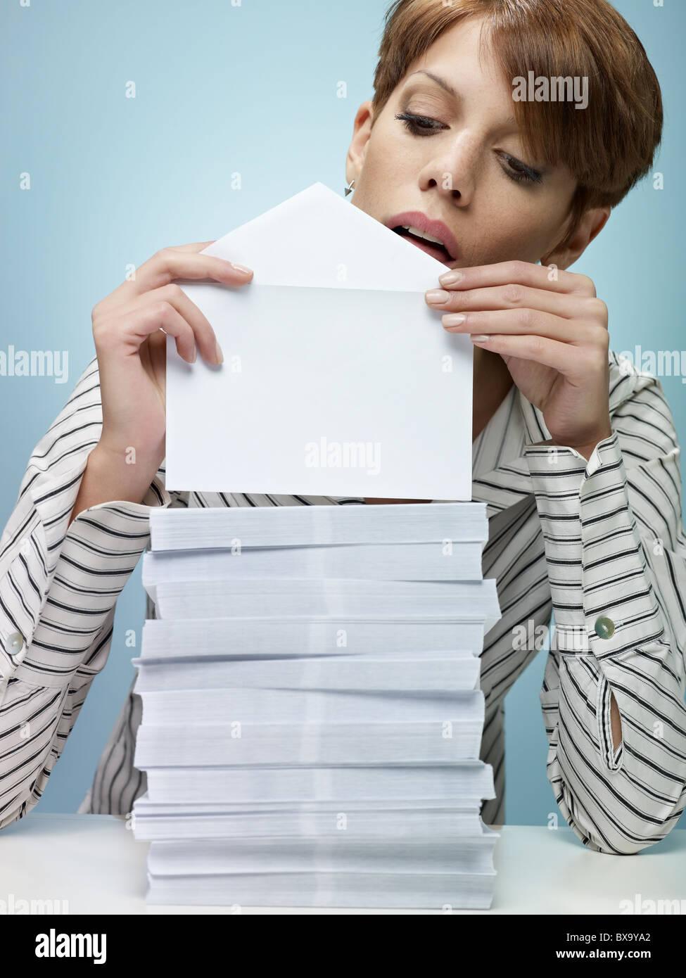 caucasian secretary closing pile of envelopes. Vertical shape, front view, waist up, copy space - Stock Image