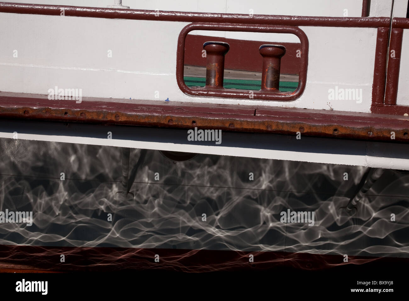 water reflections on the side of a tourist boat on Lake Garda Italy - Stock Image
