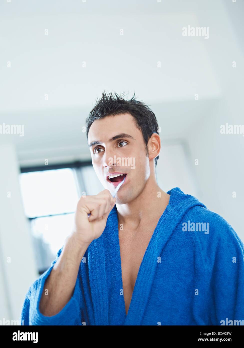 caucasian man brushing teeth in bathrobe - Stock Image