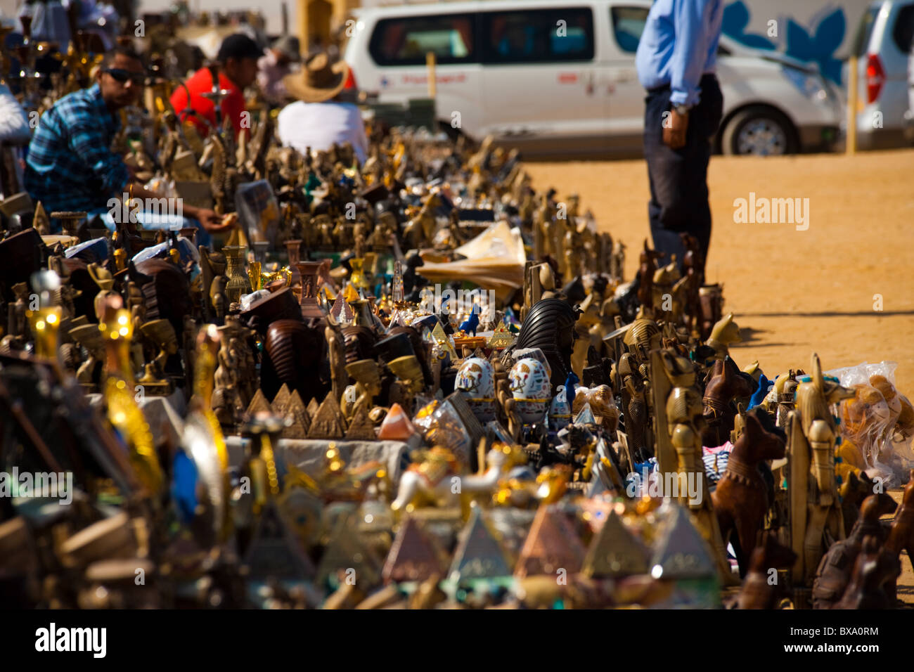 Kitschy tourist souvenirs stacked high on display at Great Pyramids viewpoint - Stock Image
