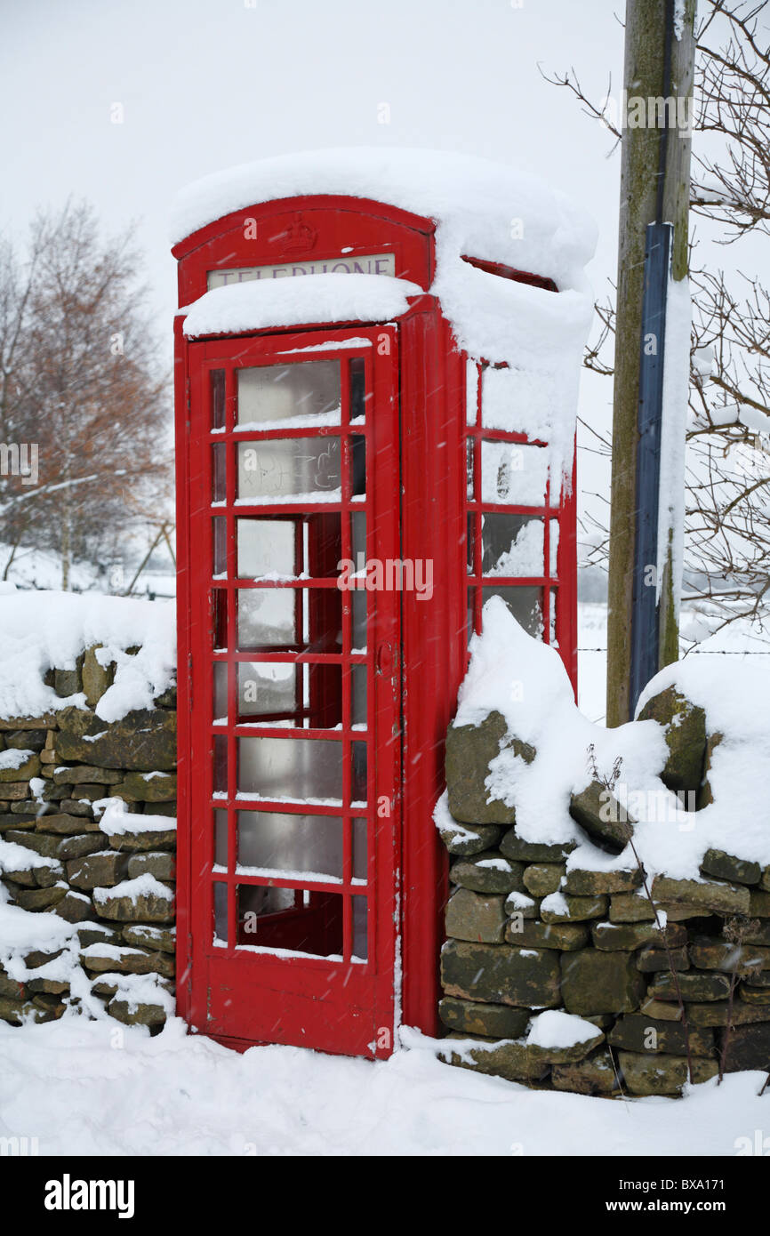 Snow covered telephone box in Honley, Holmfirth, West Yorkshire, England, UK. - Stock Image