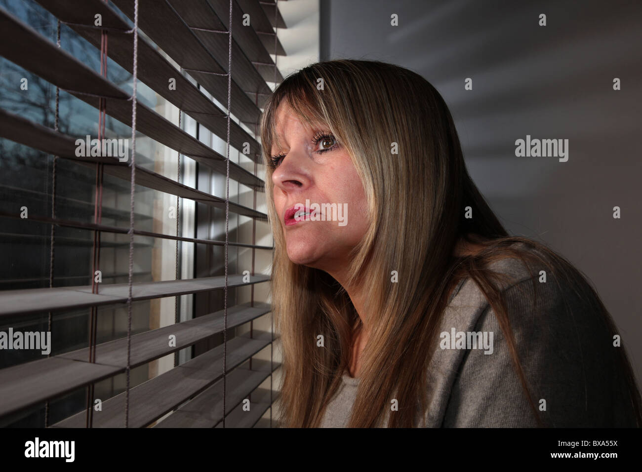Woman looking out of a window through a blind Stock Photo