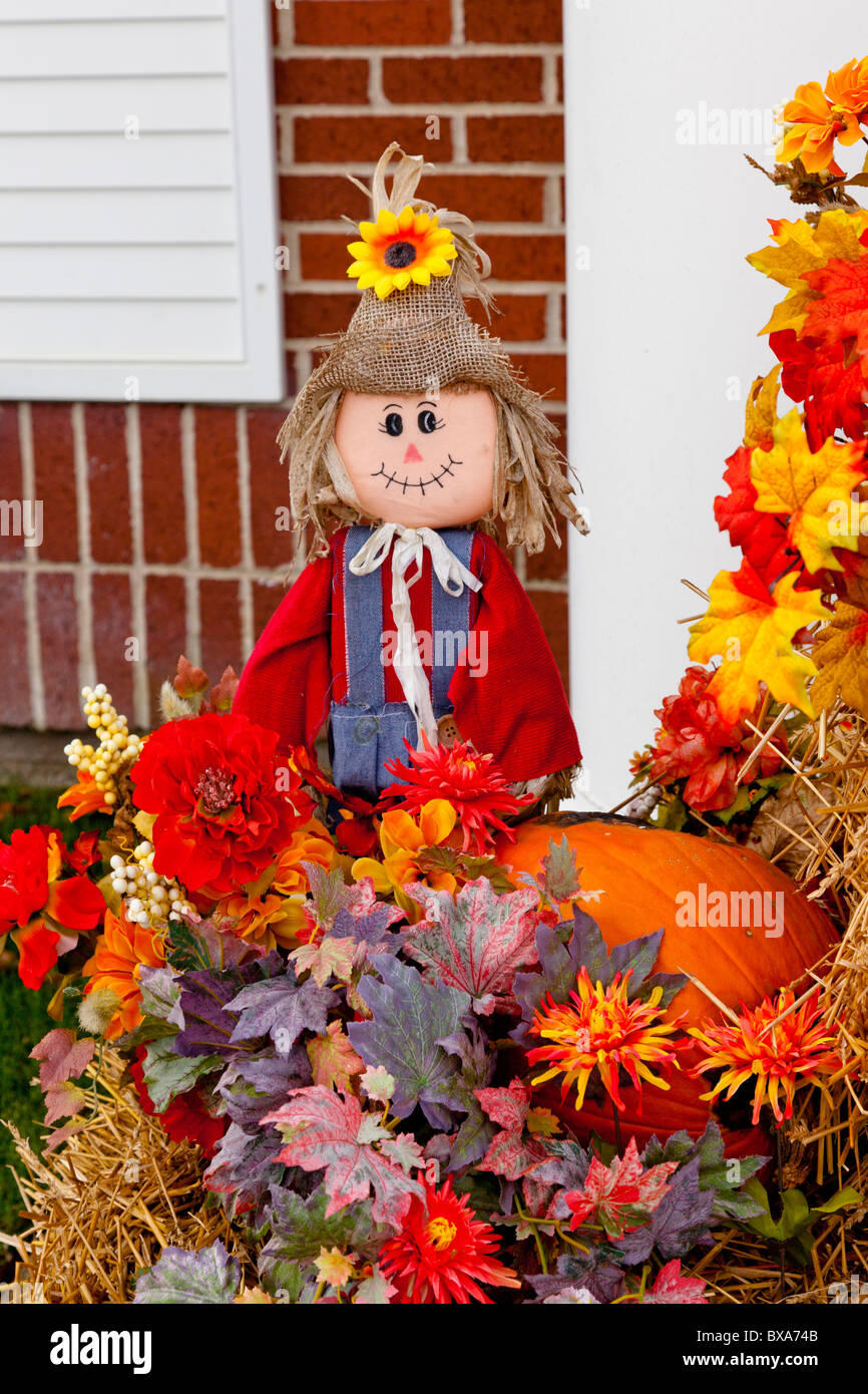 A Display Of Fall Decor With Scarecrows Pumpkins Flowers