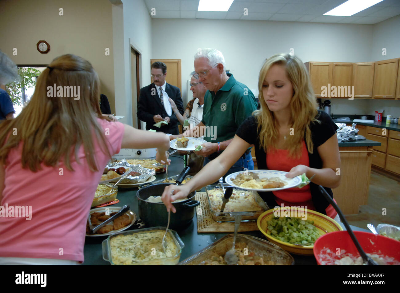 Congregation members serve themselves during potluck buffet luncheon at their church in Burnet, Texas, USA - Stock Image