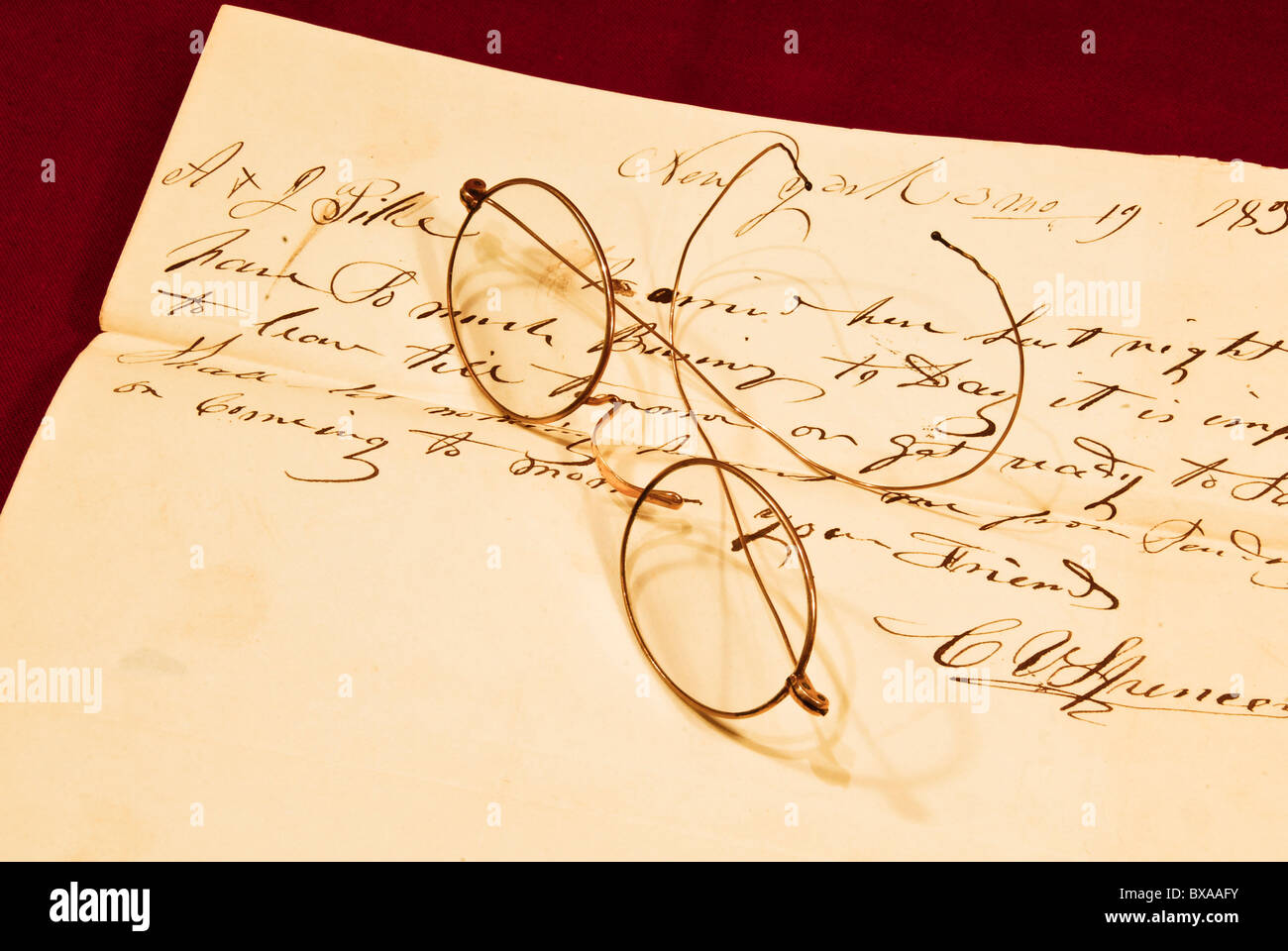 Wire-framed gold spectacles lying on a 19th century hand-written letter. - Stock Image