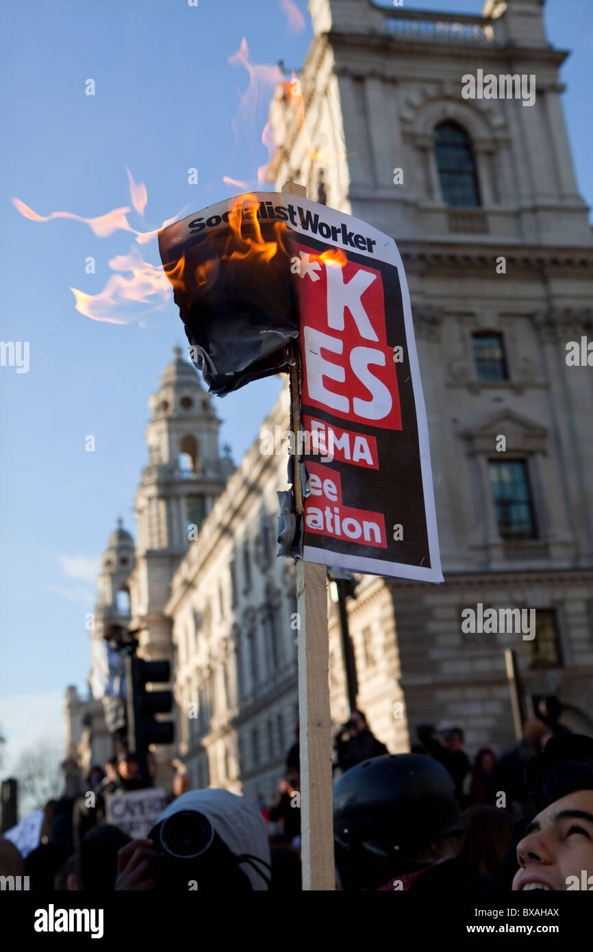 Socialist Worker placard set alight during Tuition Fees demonstration in Parliament Square - Stock Image