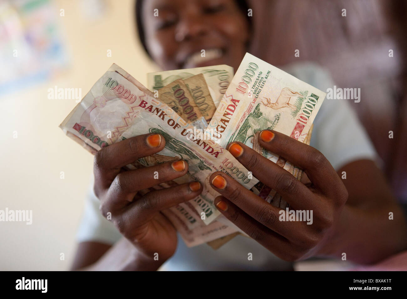 An accountant counts cash (Ugandan Shillings) in an office in Mbale, Eastern Uganda, East Africa. Stock Photo