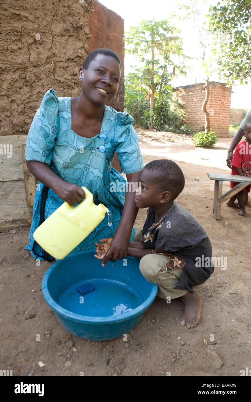 Ms. Rose Takuwa (left) teaches her son Godwin (5) hand washing in Iganga, Eastern Uganda. - Stock Image