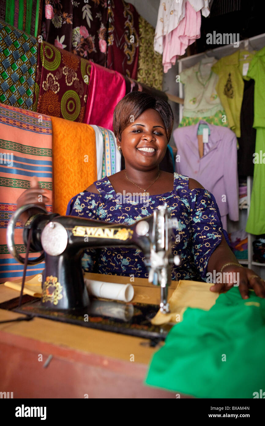 Ms. Juliet Mulebi sells clothing and performs alterations in her shop in the market in Iganga, Uganda, East Africa. - Stock Image