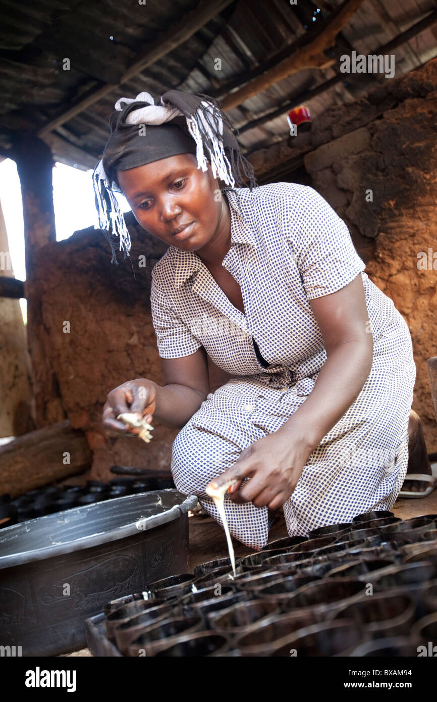 A baker (Rehama Mbabazi) pours batter into a cakepan in Mutukula Village, Iganga district, Eastern Uganda., East Stock Photo