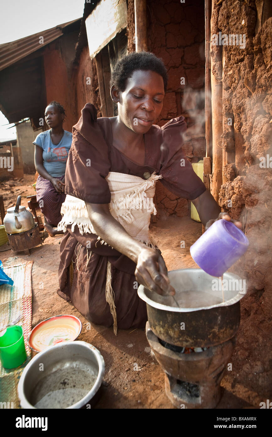 A woman (Ms. Regina Nabirye) cooks outside her small one room house in a slum in Jinja, Uganda, East Africa. - Stock Image