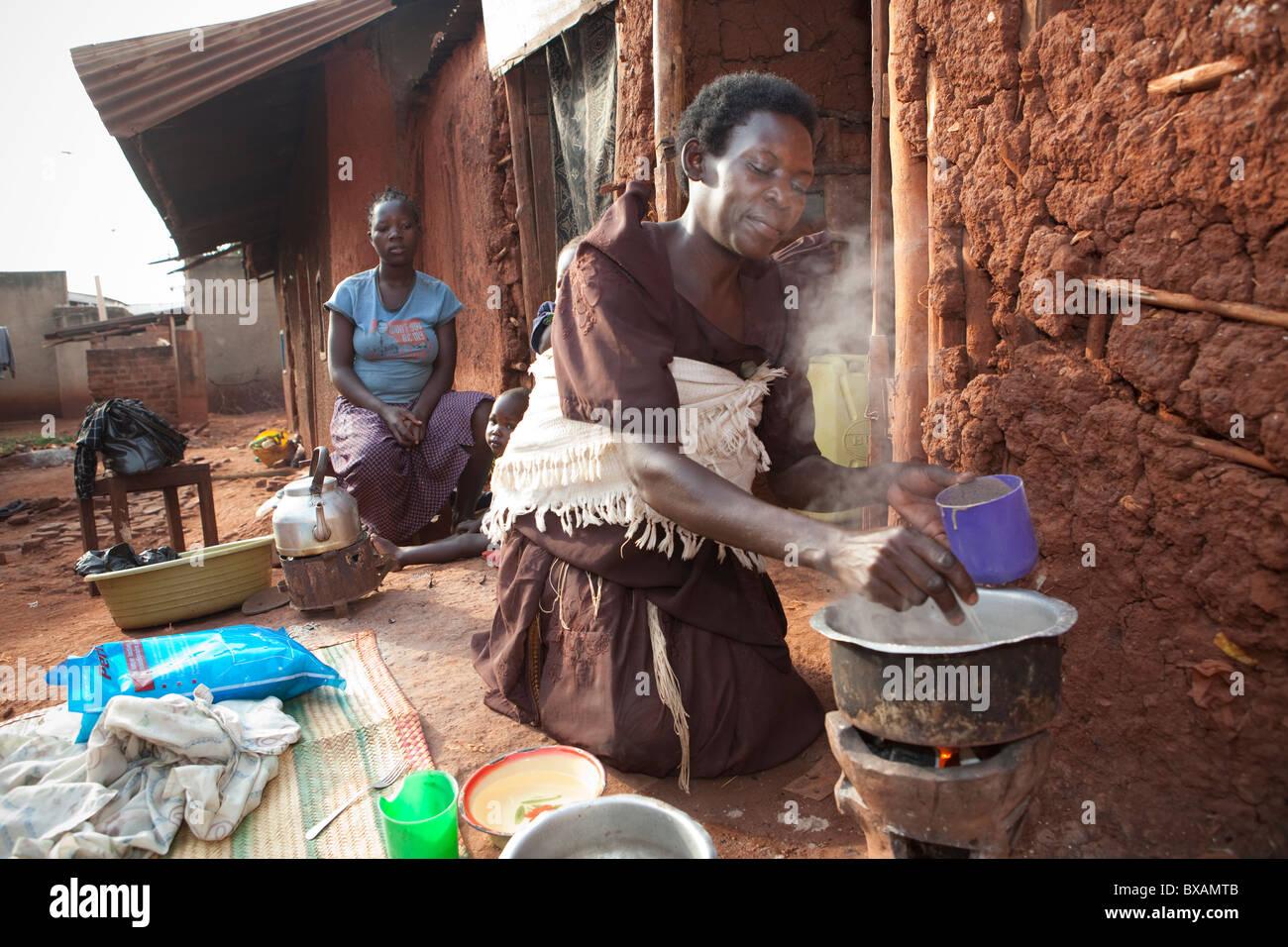 A woman (Ms. Regina Nabirye) cooks outside her small one room house in a slum in Jinja, Uganda, East Africa. - Stock Image